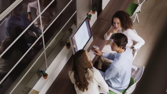 vídeos de stock e filmes b-roll de creative businesspeople discussing over computer in modern office - trabalho de design