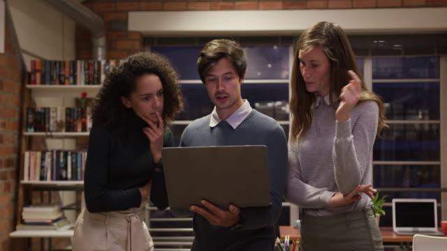 vídeos de stock e filmes b-roll de creative businesspeople discussing over laptop in modern office - trabalho de design