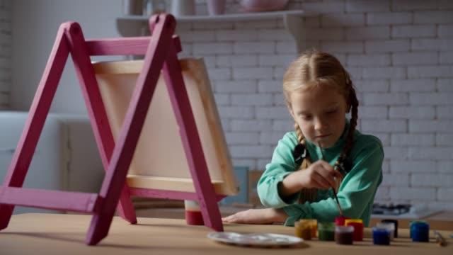 bambino creativo che scrive pittura su cavalletto in cucina - arti e mestieri video stock e b–roll