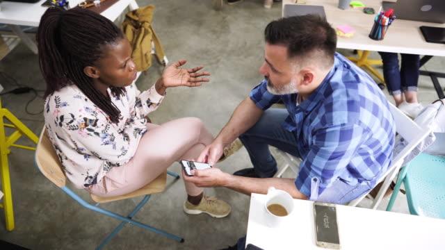colleghi creativi che chattano sul lavoro - abbigliamento casual video stock e b–roll