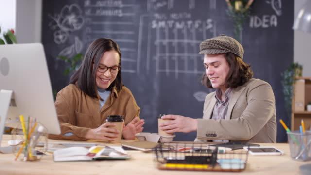 vídeos de stock e filmes b-roll de creative colleagues having coffee together in office - trabalho de design