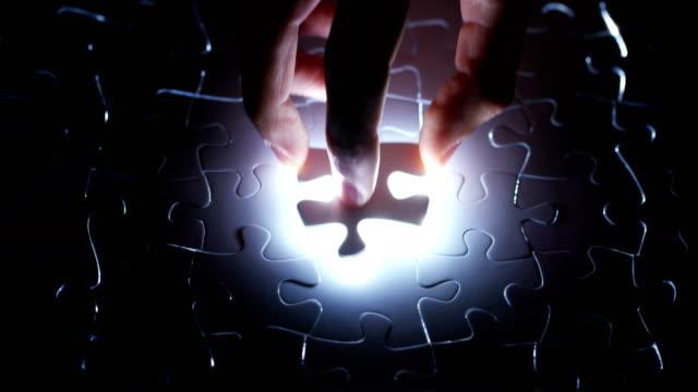 stockvideo's en b-roll-footage met een creatieve voltooit de zwart of wit licht puzzel brengen het laatste ontbrekende stuk. concept: samenwerking, samenwerking, creativiteit en access-oplossing. - legpuzzel