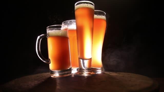 クリエイティブコンセプト。暗い色調の霧の背景に木製のテーブルの上のビールグラス。選択フォーカス ビデオ