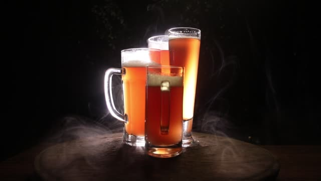 Creative concept. Beer glasses on wooden table at dark toned foggy background. Selective focus Creative concept. Beer glasses on wooden table at dark toned foggy background. Selective focus lager stock videos & royalty-free footage