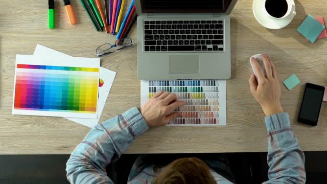 創造的なデザイナーの最初仕事、ノート パソコンを開き、レポート、トップ ビューを入力 - ブランディング点の映像素材/bロール