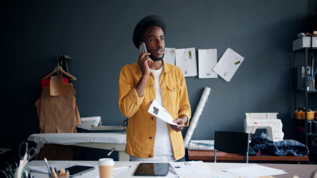 Creative designer making telephone call with smartphone talking at work Creative designer African American guy is making telephone call with smartphone talking at work enjoying business communication. People and conversation concept. independence stock videos & royalty-free footage
