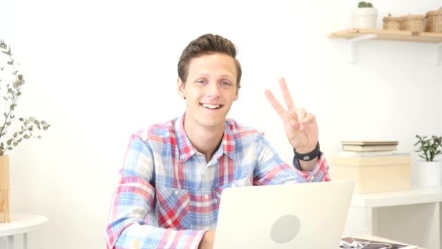 creative designer showing victory sign , job done - coinvolgimento dei dipendenti video stock e b–roll