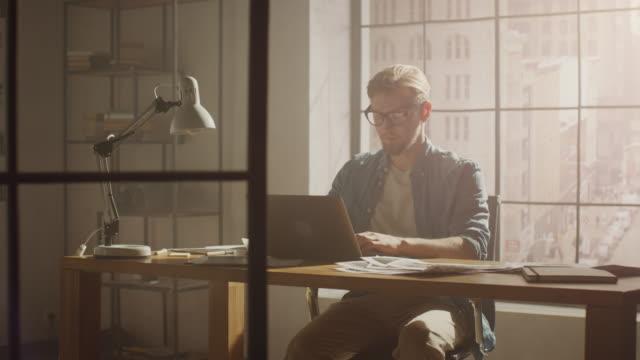 creative designer arbetar på en bärbar dator sitter vid hans skriv bord, han stänger laptop efter behandling bra dagar arbete. elegant modernt kontor med skisser och koncept som täcker väggar och stora stadsbilden view - 4k upplösning bildbanksvideor och videomaterial från bakom kulisserna