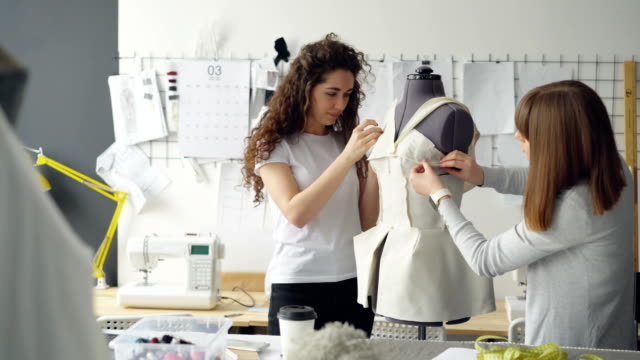 Creative female clothing designers are pinning cut out pieces of fabric to dummy while tailoring women's garment in modern studio. Ladies are focused on their work.