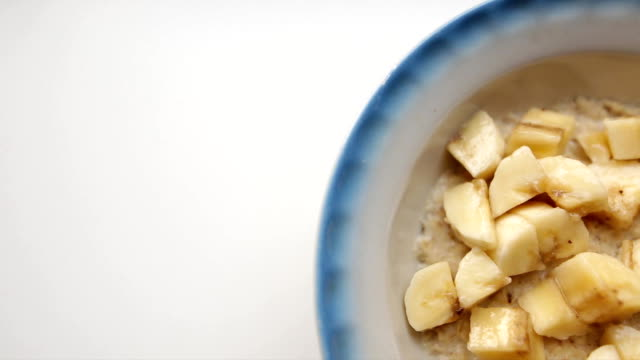 Creative food background. Healthy breakfast, oatmeal porridge with milk and fresh bananas. Oat flakes filled with milk in a faience dish on a white background. Organic food for good health. video