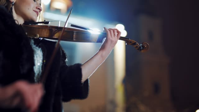 a creative girl in a black coat is playing the violin a romantic melody on the background of light from an evening lantern in the city. - praticare video stock e b–roll