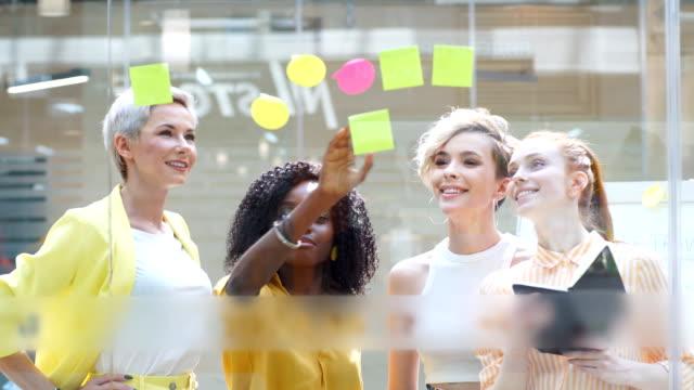 kreatives glamour-team schreibt auf aufkleber an büroglaswand - post it stock-videos und b-roll-filmmaterial