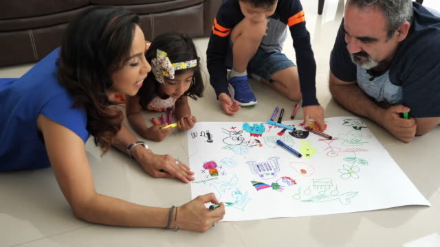 Creative Latin parents drawing with children at home and laughing.