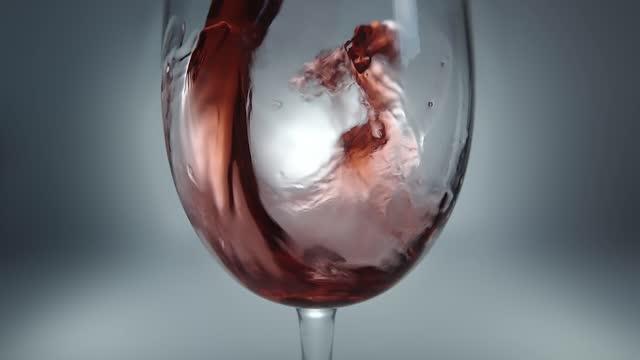 kreative makro-zeitlupe rohvideo von rotwein in ein glas gießen. glas mit gießendem rotwein aus nächster nähe. - cabernet sauvignon traube stock-videos und b-roll-filmmaterial