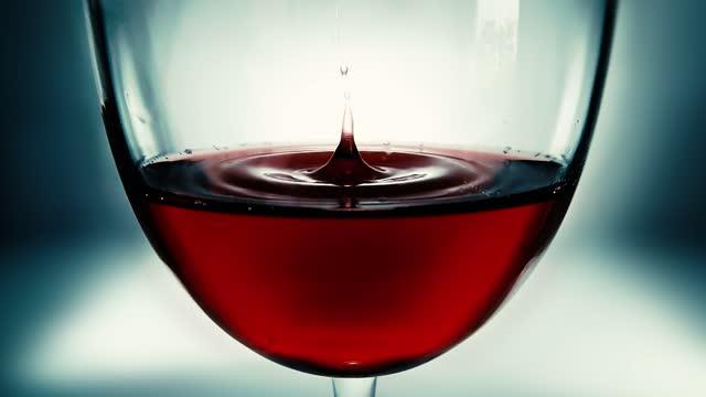 kreative makro-zeitlupe video von rotwein in einem glas und einen fallenden tropfen wein. ein glas mit langsam fallenden tropfen wein aus nächster nähe. alte retro grunge vintage-stil. - cabernet sauvignon traube stock-videos und b-roll-filmmaterial