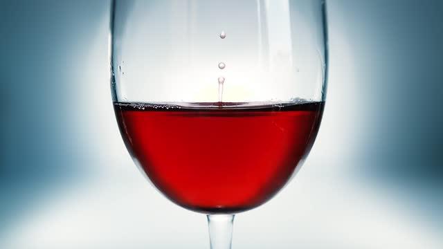 kreative makro-zeitlupe video von rotwein in einem glas und einem fallenden tropfen wein. ein glas mit einem langsam fallenden tropfen wein aus nächster nähe. - cabernet sauvignon traube stock-videos und b-roll-filmmaterial