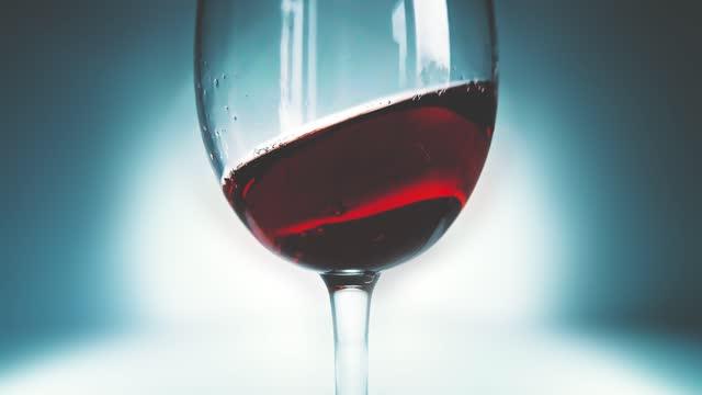 kreative makro-zeitlupe video von rotwein spritzen in einem glas von seite zu seite wie wellen. glas mit spritzwein aus nächster nähe. alte retro grunge vintage-stil mit einem angenehmen, leicht weich verblasst. - cabernet sauvignon traube stock-videos und b-roll-filmmaterial
