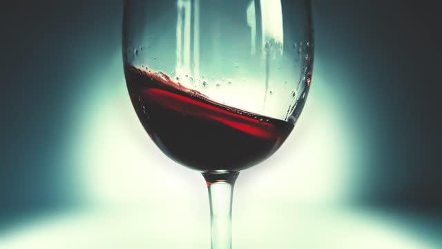 творческий макро медленное движение видео красного вина брызг в стакане из стороны в сторону, как волны. стекло с брызг вина крупным планом. - декантер стоковые видео и кадры b-roll