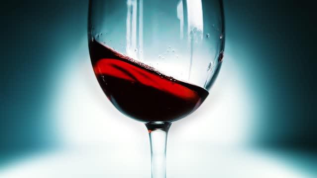 kreative makro-zeitlupe video von rotwein spritzen in einem glas von seite zu seite wie wellen. glas mit spritzwein aus nächster nähe. alte retro grunge vintage-stil. - cabernet sauvignon traube stock-videos und b-roll-filmmaterial