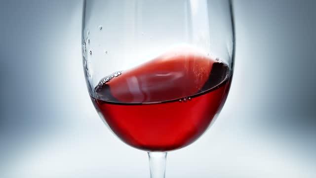 kreative makro-zeitlupe video von rotwein spritzen in einem glas von seite zu seite wie wellen. glas mit spritzwein aus nächster nähe. - cabernet sauvignon traube stock-videos und b-roll-filmmaterial