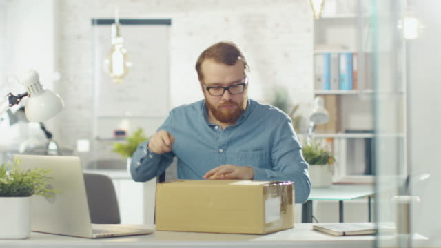 Creative Man Opens Up Parcel While Sitting in His Bright and Modern Office. video