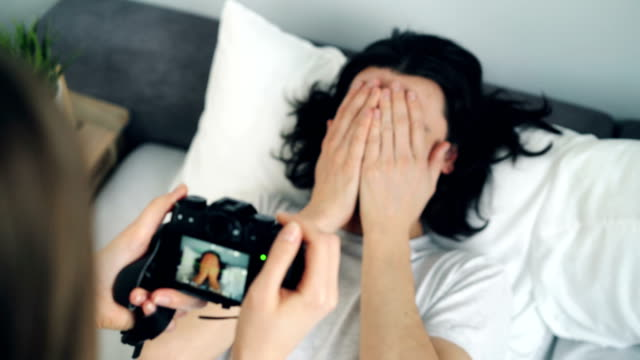 Creative man posing in bed with funny faces while woman taking photo with camera Creative young man is posing in bed with funny faces and long hair while woman is taking photo with digital camera. Hobby, photography and fun concept. long hair stock videos & royalty-free footage
