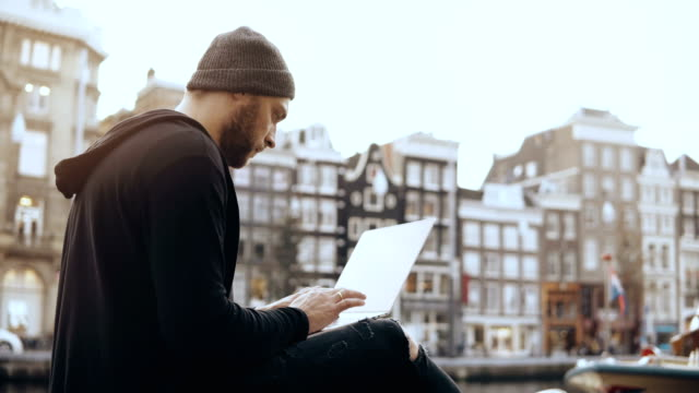 4k creative man sitting with laptop in the street. working mobile office. amsterdam old town. atmospheric cityscape - entrepreneur stock videos and b-roll footage