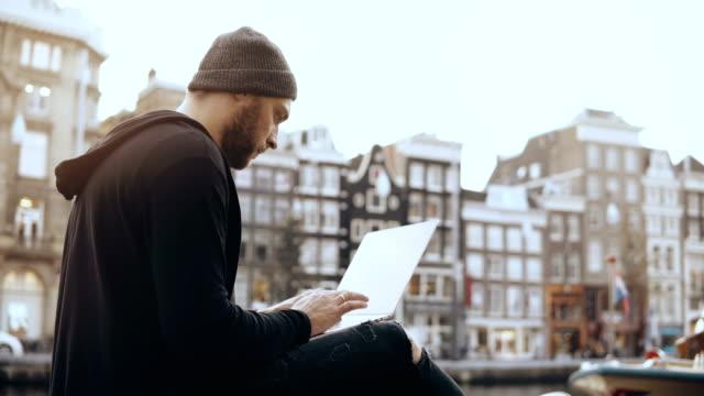 vidéos et rushes de 4k creative homme assis avec ordinateur portable dans la rue. travail de bureau mobile. vieille ville d'amsterdam. atmosphère paysage urbain - entrepreneur