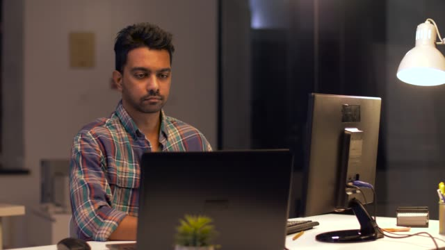 kreativa man med dator arbetar på natten kontor video