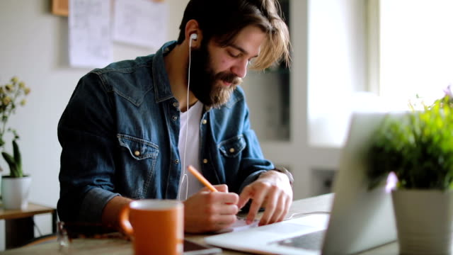 Creative man working in his modern home office Man working at modern office headphones stock videos & royalty-free footage
