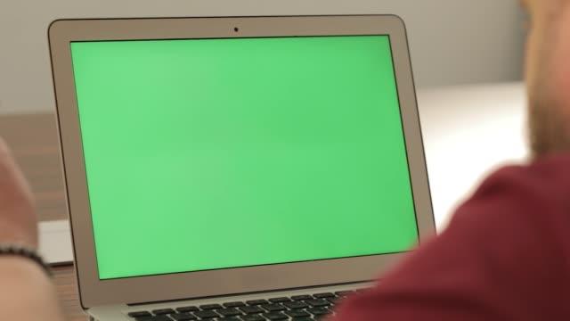 創造的なマネージャーの仕事。ビジネス コンセプトです。クロマキー グリーン画面と彼のラップトップ pc に自信を持って若い男 - パソコン点の映像素材/bロール