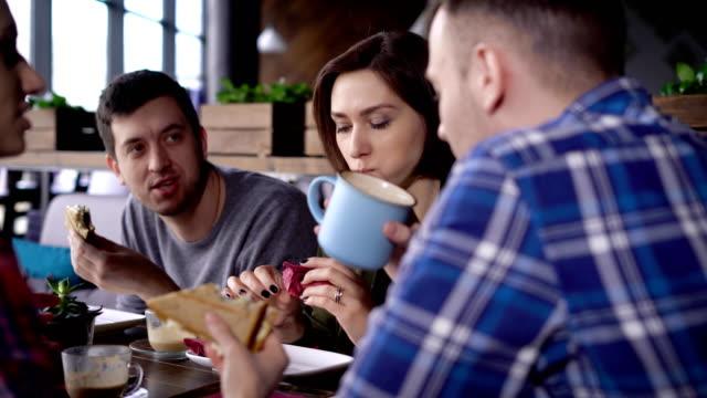 vídeos de stock, filmes e b-roll de criativos modernamente vestidos amigos conheceram na hora do almoço durante o intervalo. meninos e meninas saiu do escritório para comer uma sandes e beber café. amigos se comunicar sobre vários temas em seu café favorito - antepasto