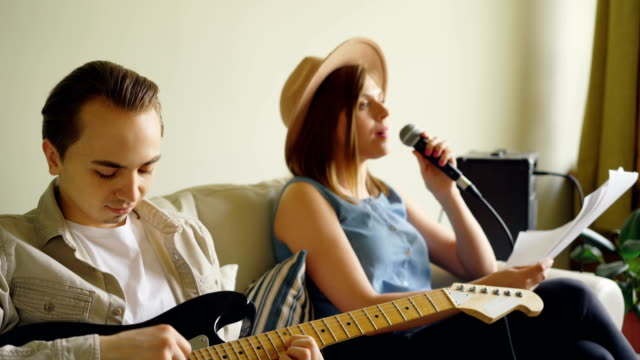 creative musical duet is practising at home woman is singing in microphone and man is playing the guitar. young cheerful people are wearing casual clothes. - lega sportiva amatoriale video stock e b–roll