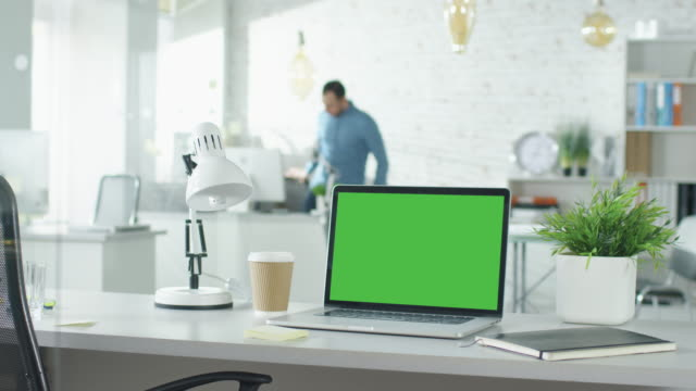 Creative Office Shot of Green Screened Laptop Standing on the Table with Nobody Working on It. In the Background Man Comes in and Sits at His Workplace Starts Working. video