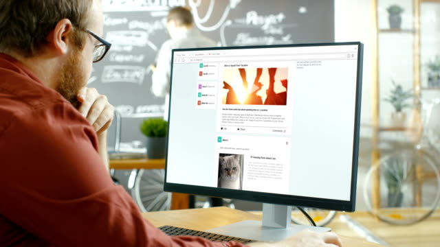 creative office worker browsing social network pages, he scrolls through his wall on a personal computer. in the background stylish creative agency studio with blackboard wall. - social media стоковые видео и кадры b-roll