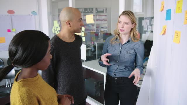 stockvideo's en b-roll-footage met creatief team brainstormen samen in office - omgeving