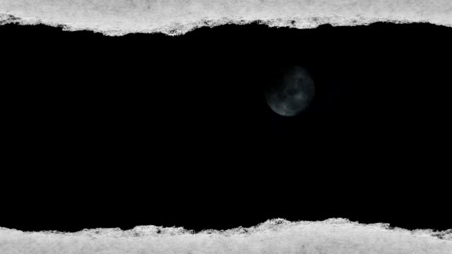 Creative time laps video of a glowing full moon in the night sky with floating clouds, which is visible through a hole with torn edges in old retro grunge vintage paper.