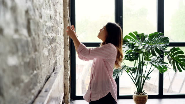 creative woman is decorating her loft style apartment choosing place on brick wall for beautiful picture and marking spot with pencil. creativity and interior concept. - foto video stock e b–roll