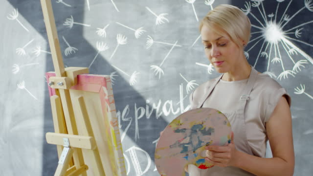 creative woman painting in studio - cavalletto attrezzatura per arti e mestieri video stock e b–roll