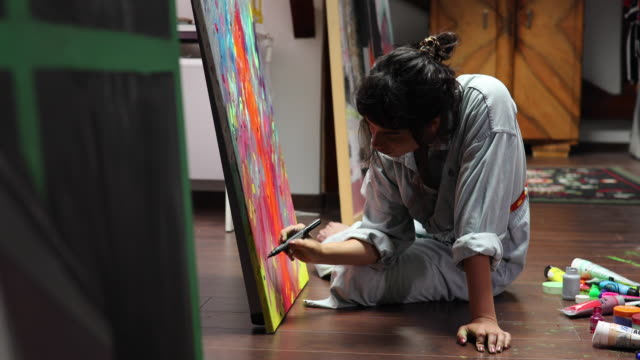 Creative young artist painting at home Young artist sitting on the floor and painting hobbies stock videos & royalty-free footage