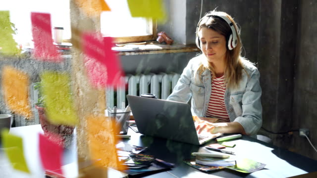 Video Creative young businesswoman is listening to music in headphones dancing while working at desk with laptop in modern office. Glass with colored stickers in foreground.
