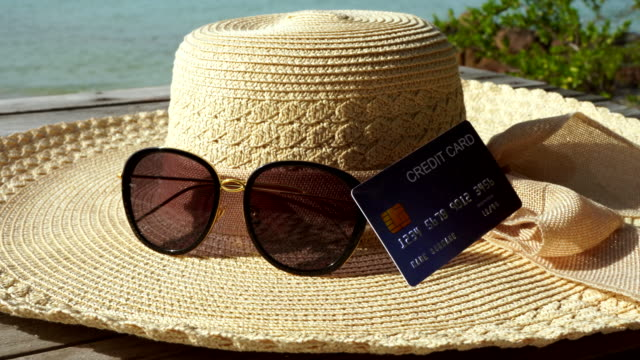 credit card and accessories for the holiday, sun glasses and sea hat on the wood bridge, copy space. - credit card filmów i materiałów b-roll