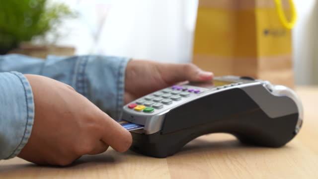 お金の取引のためのクレジットカード機。pos端末を通してクレジットカードスワイプで男の手とピンコードを入力します。電子マネーの銀行サービス。財務上の成功と安全性。 - クレジット決済点の映像素材/bロール