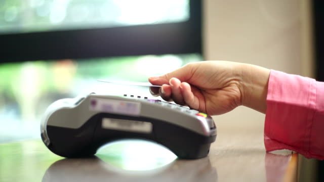 vídeos de stock e filmes b-roll de credit card payment with nfc technology in cafe. - paying with card contactless