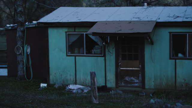 stockvideo's en b-roll-footage met griezelig verlaten huis in de bossen schemering - verlaten slechte staat