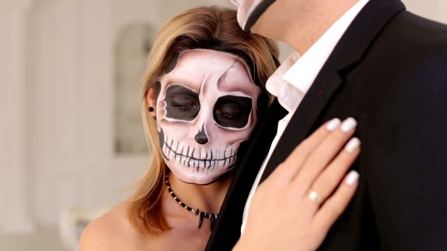 Creepy couple of actors with scary Halloween makeup in vintage costumes.