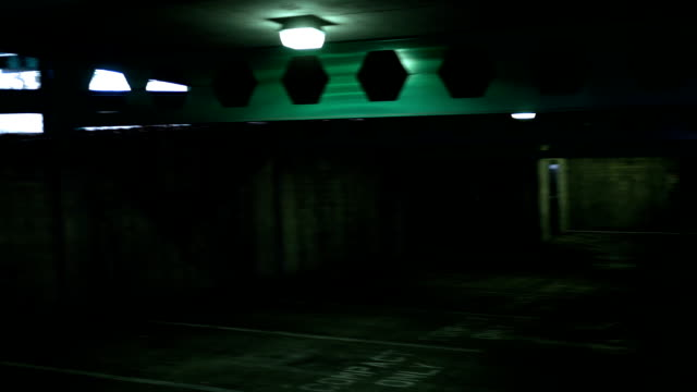 POV of creepy empty dark parking garage in basement level
