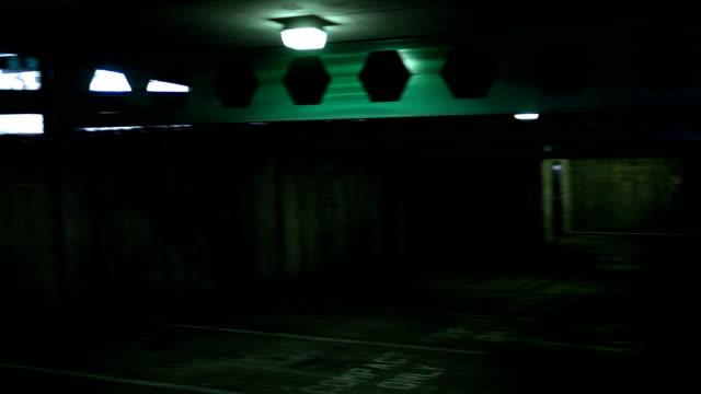 POV of creepy empty dark parking garage in basement level video