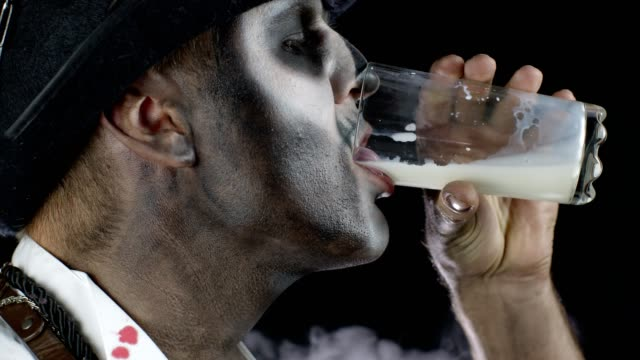 Creepy man with skeleton makeup in white shirt. Guy looking at camera, drinks milk from a glass