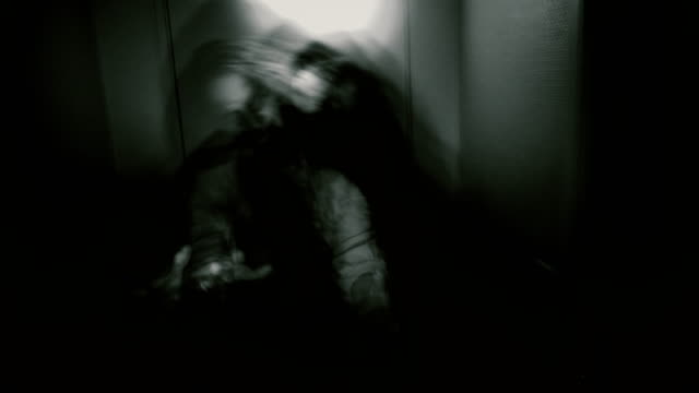 Creepy POV nightmare. A man enters dark hallway with flashlight and encounters a monster. Exorcism, ghost or evil apparition.